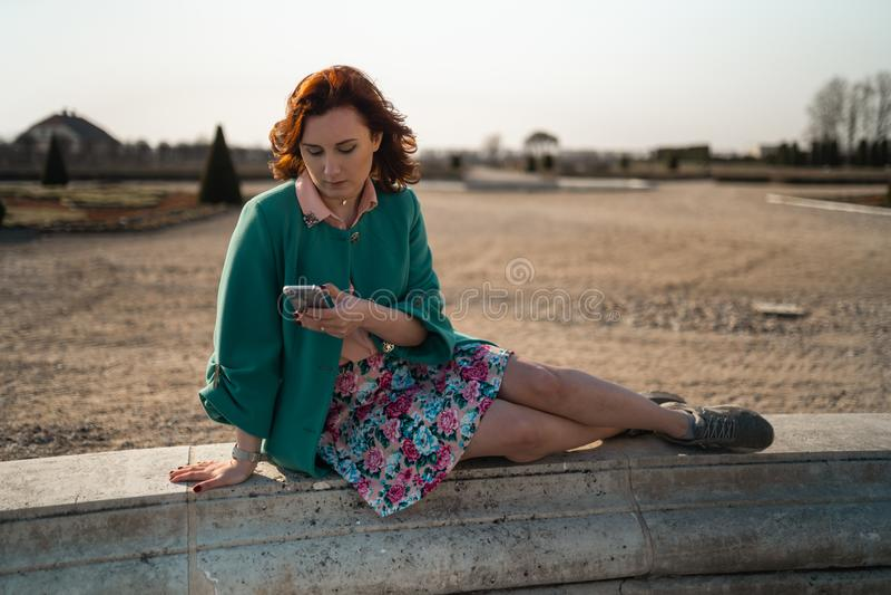 年轻女人在宫殿公园使用电话坐喷泉 免版税库存照片