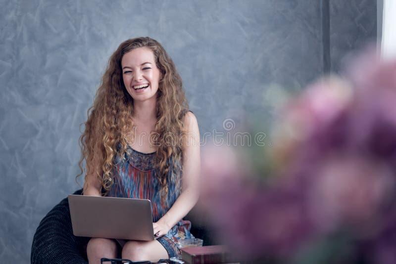年轻女人在家与手提电脑一起使用 库存照片