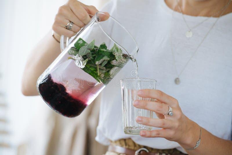 年轻女人在家倒从水罐的新鲜的柠檬水入玻璃 库存图片