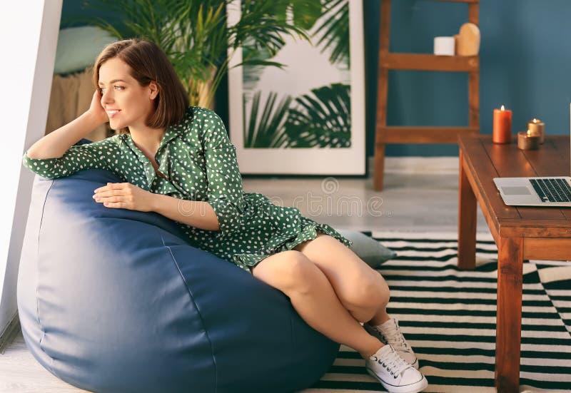 年轻女人在家坐装豆子小布袋椅子 免版税库存照片