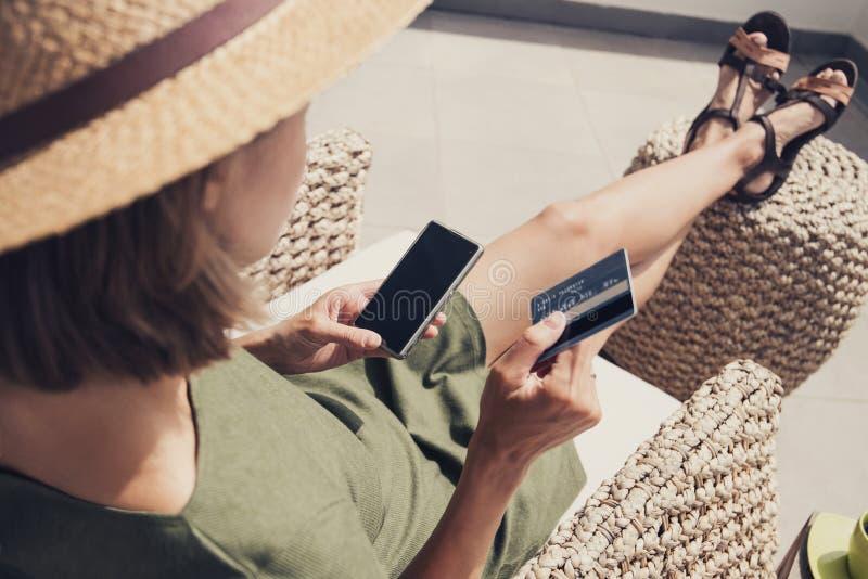 年轻女人在度假使用电话和信用卡的 在线购物概念 免版税库存图片