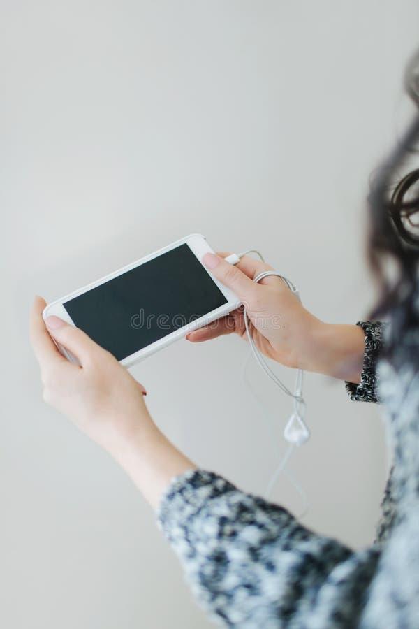 年轻女人在手上的拿着白色智能手机 免版税库存照片