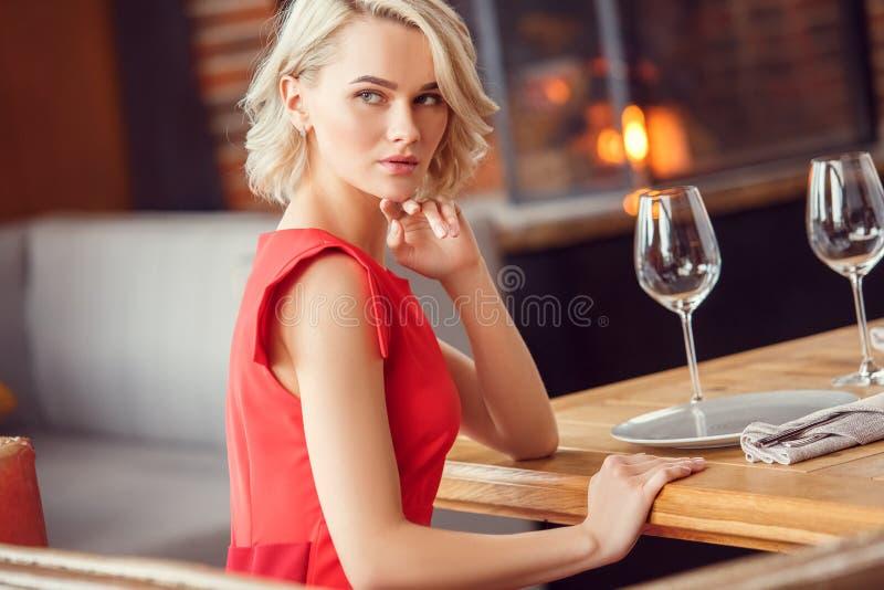 年轻女人在日期在坐的餐馆看肉欲的窗口 库存图片