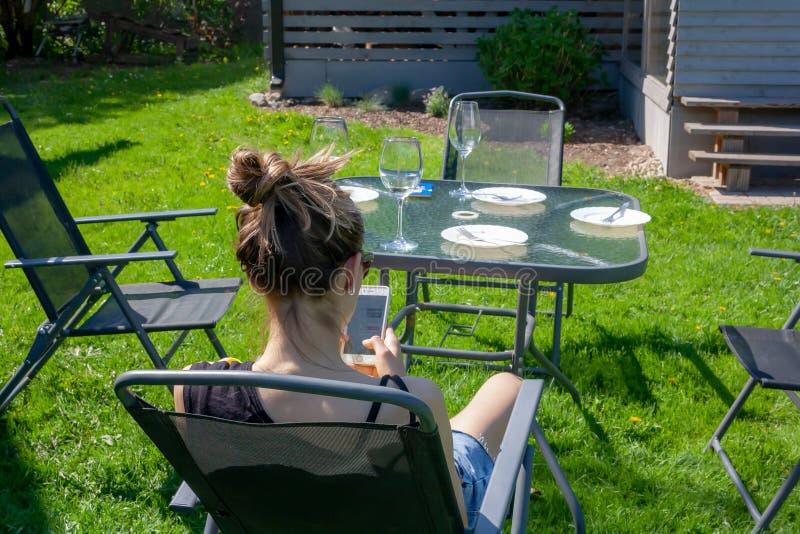年轻女人在有一个电话的一个庭院里坐在她的手上 从后面 库存图片