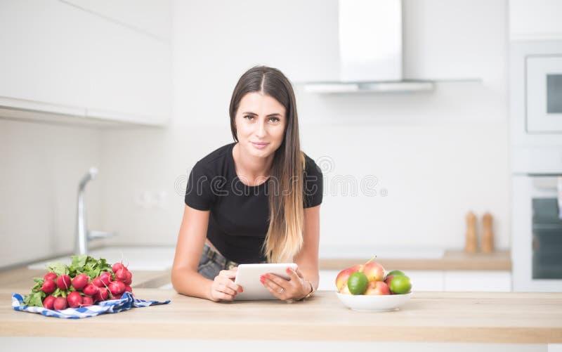 年轻女人在有片剂的家庭厨房里 免版税图库摄影