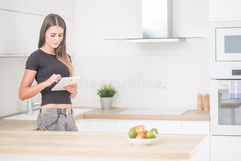 年轻女人在有片剂的家庭厨房里 图库摄影
