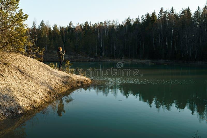 年轻女人在波罗的海国家拍旅行照片-拉脱维亚- Meditirenian样式的美丽的绿松石湖颜色- 免版税库存照片