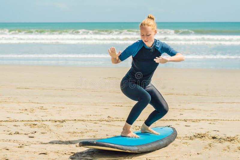 年轻女人在海浪训练站立在第一个冲浪的教训前 图库摄影