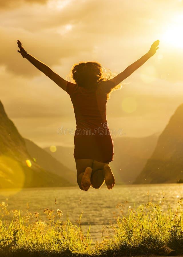 年轻女人在湖跳 免版税库存图片