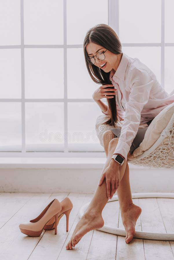 年轻女人在腿的感觉疼痛在工作场所 库存图片
