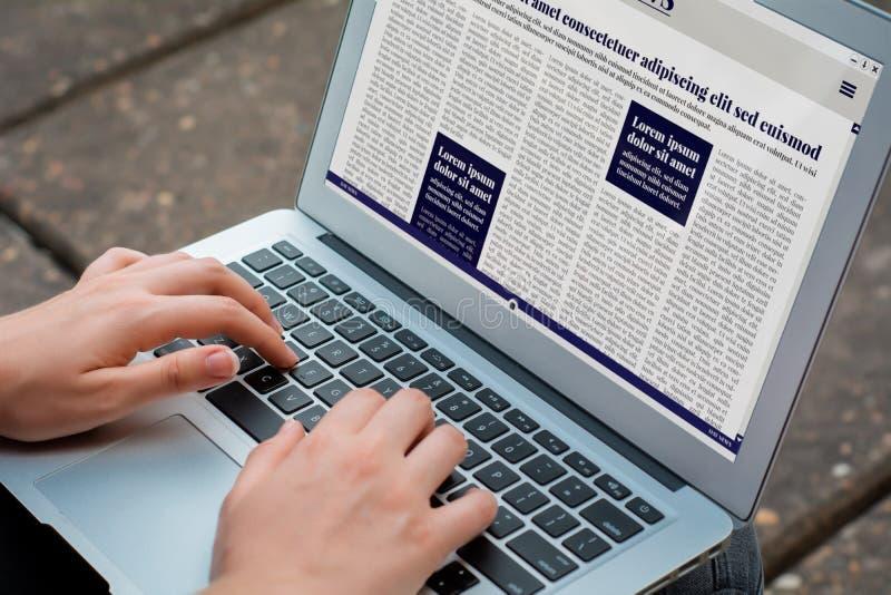 年轻女人在膝上型计算机的读书超大事件特写镜头  免版税库存图片