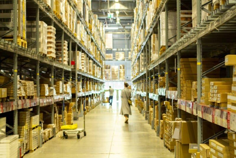 年轻女人在自助商店的仓库里选择物品 纸板箱和包装物品 免版税图库摄影