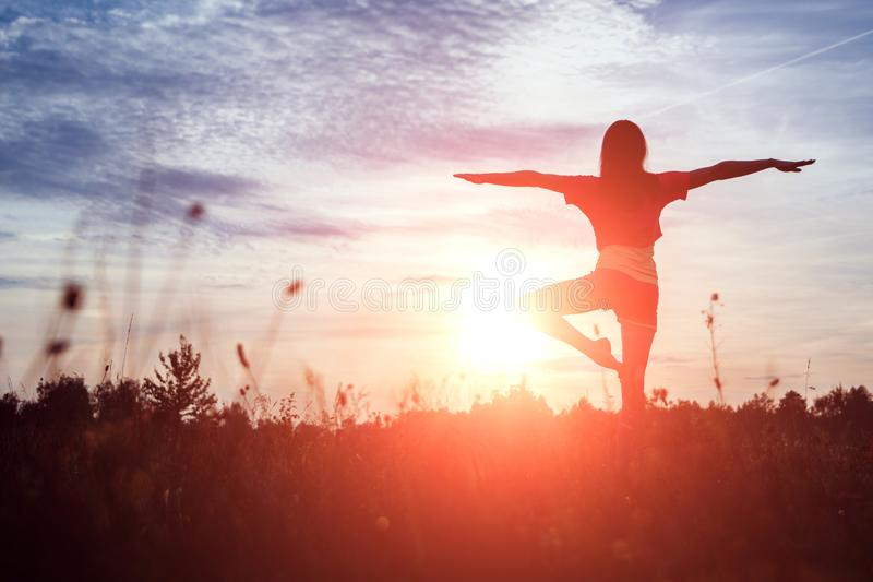 年轻女人在自然的剪影瑜伽在日落 新鲜空气,健康生活方式,拷贝空间 魔术背景 免版税库存图片
