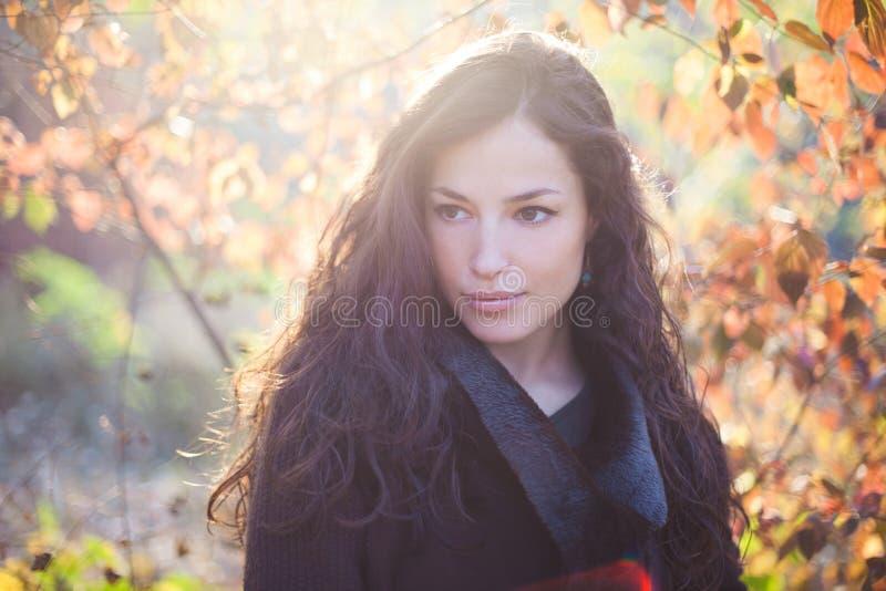 年轻女人在衣服暖和室外自然ligh的秋天画象 库存照片