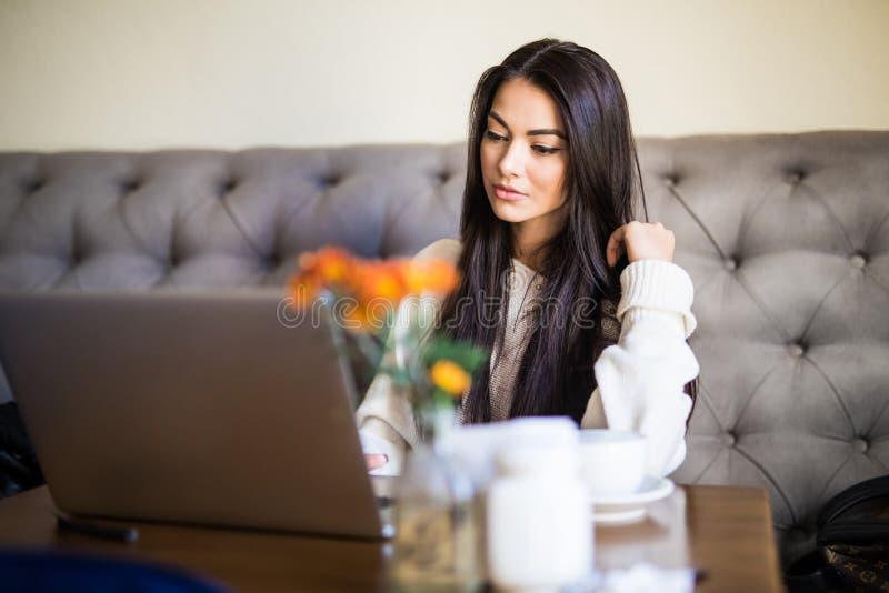 年轻女人在运作的咖啡馆食用一杯咖啡和坐手提电脑 库存照片