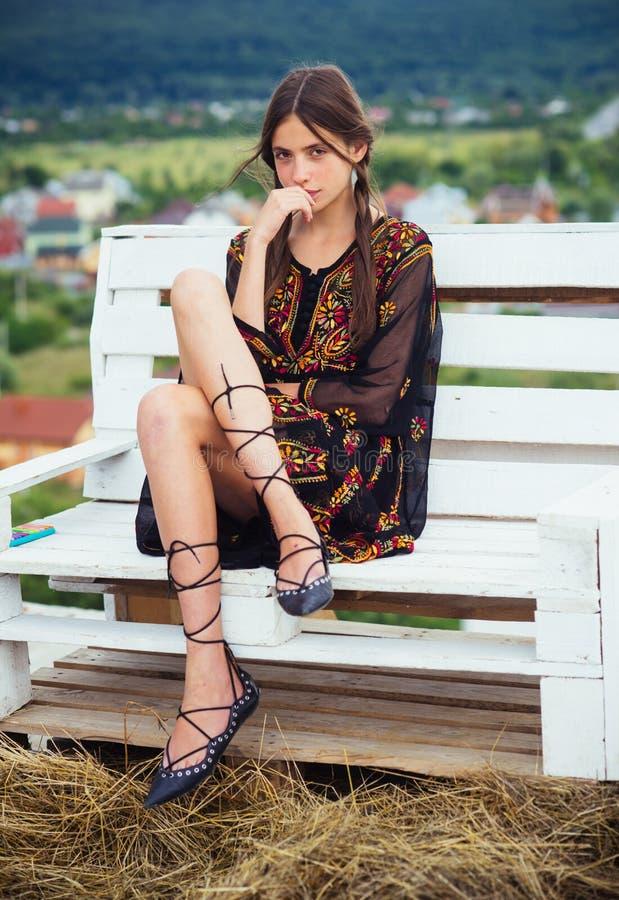 年轻女人坐在自然风景,旅行癖的长凳 库存图片