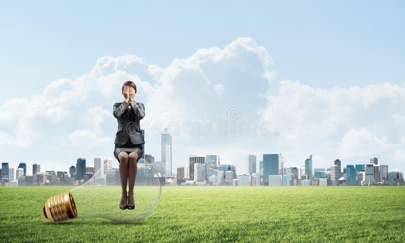 年轻女人坐大电灯泡 免版税库存照片