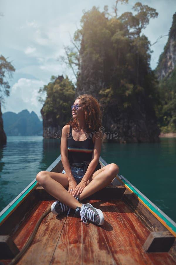 年轻女人坐小船,当在cheow lan湖,Khao Sok国立公园时的游览 免版税图库摄影