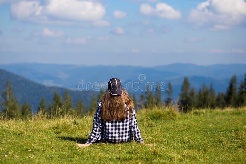 年轻女人坐平安地注视低早晨云彩的山上面 免版税库存照片
