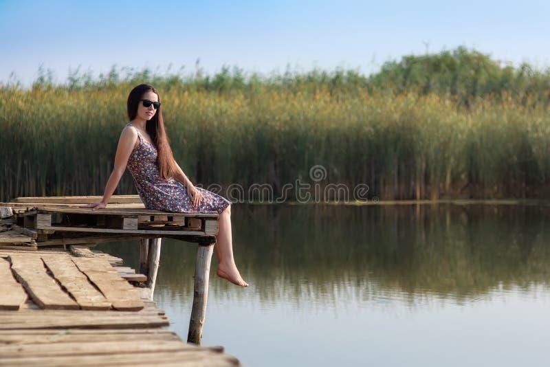 年轻女人坐木桥 免版税库存照片