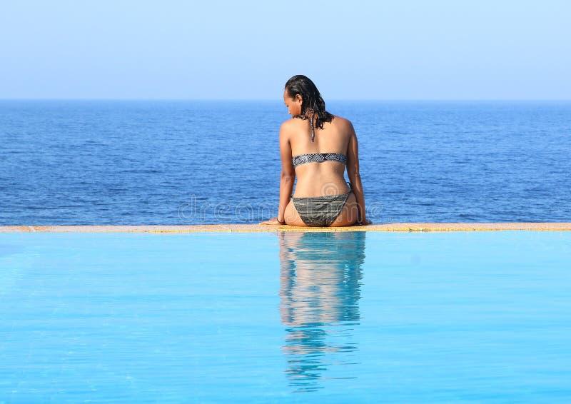 年轻女人坐水池边缘由海 库存图片