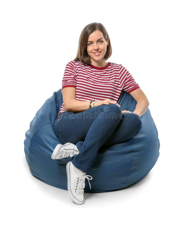 年轻女人坐装豆子小布袋椅子反对白色背景 库存照片