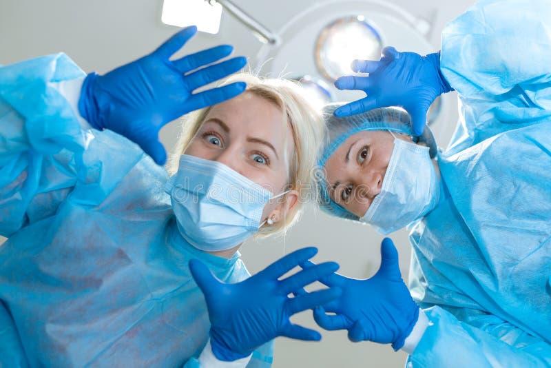 年轻女人外科医生滑稽哄骗在手术室背景的照相机 免版税库存图片