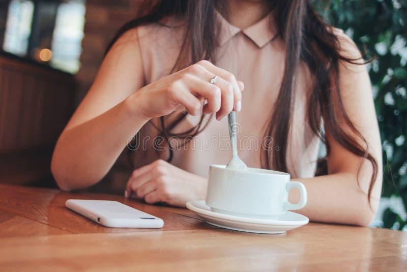 年轻女人女孩庄稼照片有咖啡的或茶,坐在咖啡馆 免版税库存图片