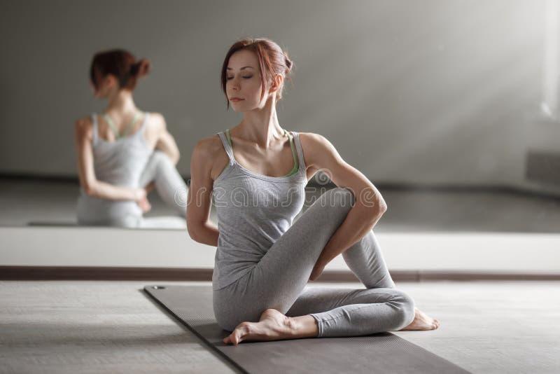 年轻女人实践的瑜伽在做美好的asana锻炼的轻的屋子里 库存图片