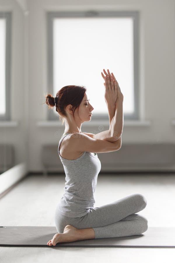 年轻女人实践的瑜伽在做美好的asana锻炼的轻的屋子里 图库摄影