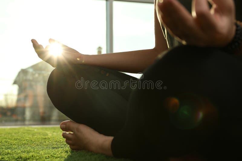 年轻女人实践的瑜伽在被日光照射了屋子里 免版税库存照片
