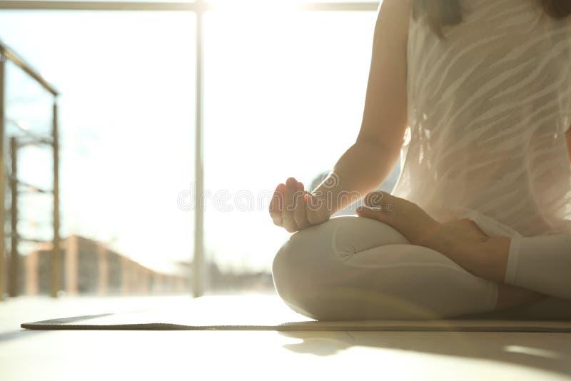 年轻女人实践的瑜伽在被日光照射了屋子,与空间的特写镜头里为 免版税图库摄影