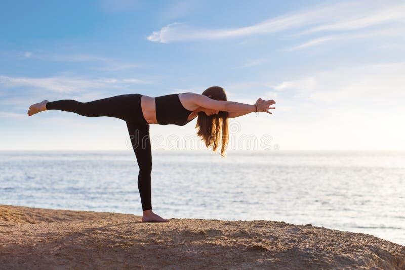 年轻女人实践的瑜伽asana姿势在海的早晨 免版税库存照片
