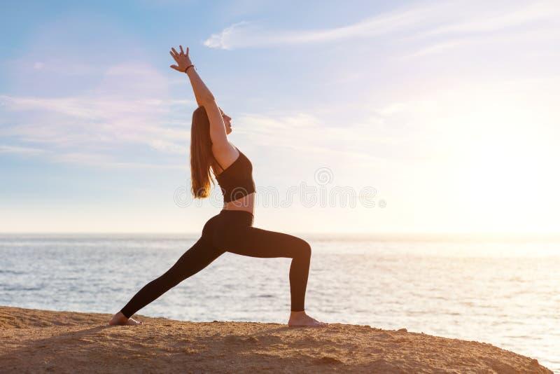 年轻女人实践的瑜伽asana姿势在海的早晨 免版税库存图片