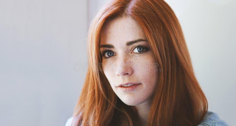 年轻女人室内画象有红色头发和雀斑的 免版税库存图片
