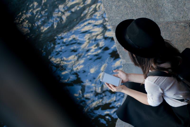 年轻女人帽子的和有背包的在城市走并且使用智能手机 免版税库存照片