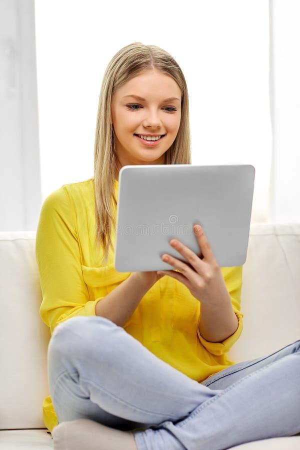 年轻女人或十几岁的女孩有平板电脑的在家 免版税库存图片
