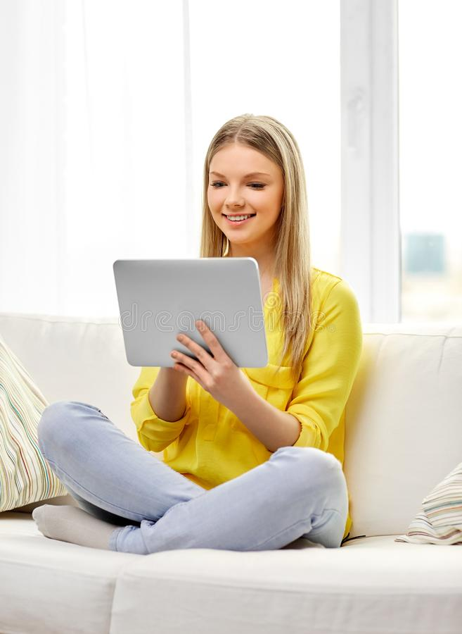 年轻女人或十几岁的女孩有平板电脑的在家 免版税库存照片