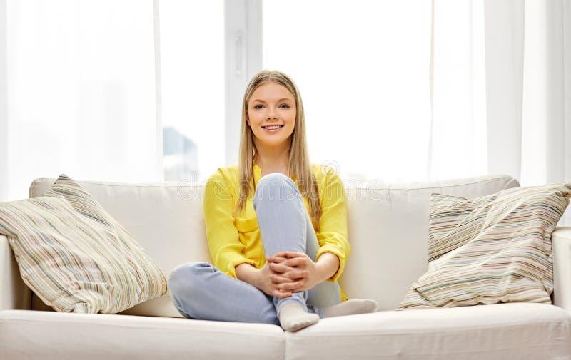 年轻女人或十几岁的女孩沙发的在家 免版税库存照片