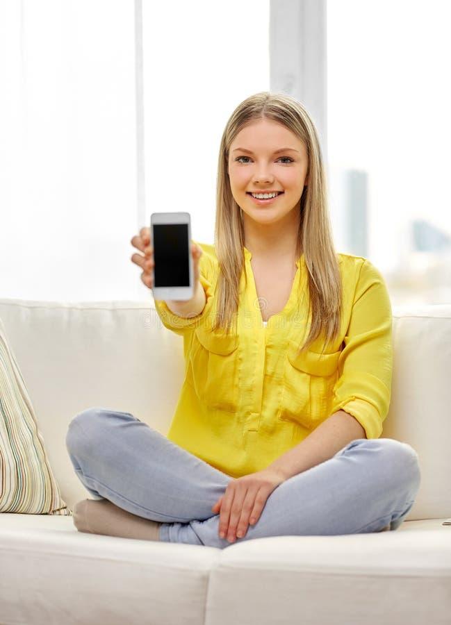 年轻女人或青少年的女孩有智能手机的在家 免版税库存照片