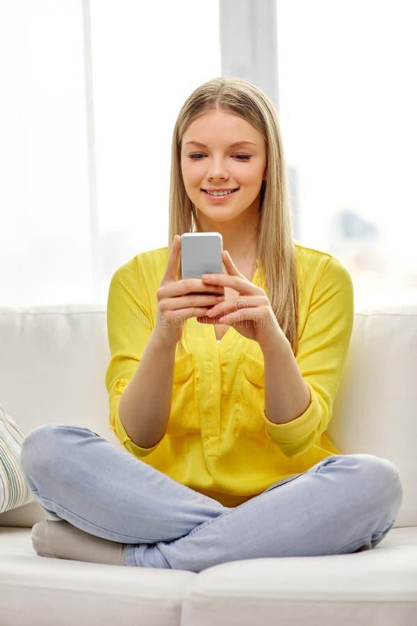 年轻女人或青少年的女孩有智能手机的在家 库存图片