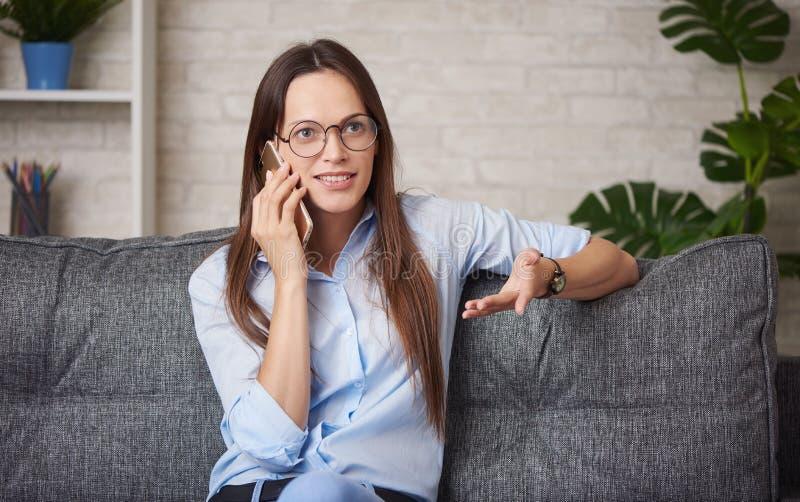 年轻女人戴圆的眼镜谈话在智能手机 库存图片