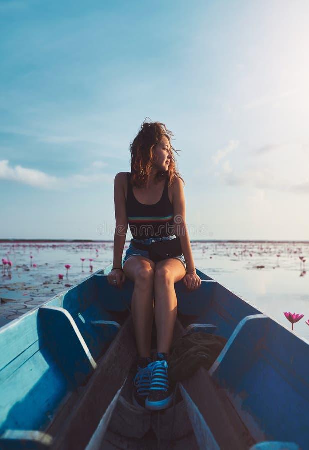 年轻女人户外画象坐在thale noi湖的蓝色小船一会儿游览 免版税图库摄影