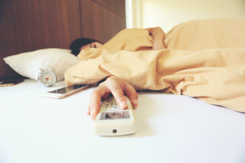年轻女人手举行遥远的空调和在家睡觉在卧室 免版税库存图片