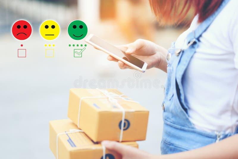 年轻女人手藏品智能手机和把与兴高采烈的面孔标志和绿色标志的校验标志放在交付上五个星  库存图片