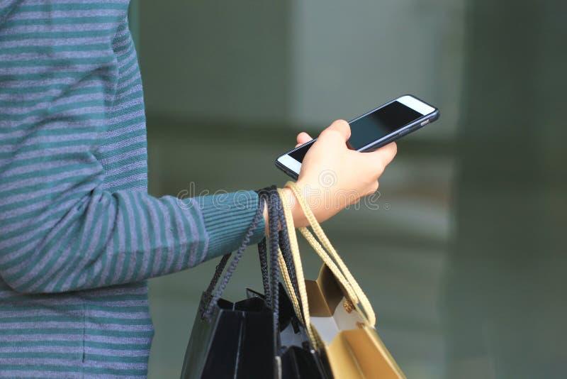年轻女人手藏品智能手机和购物带来有身分的在百货店 库存图片