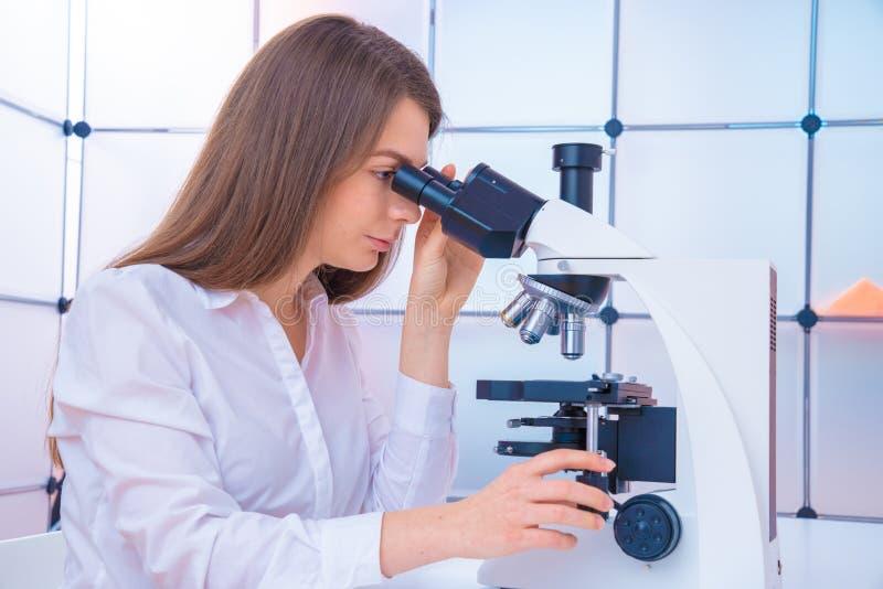 年轻女人技术员在癌症研究实验室审查一个组织学样品,一个切片检查法 免版税图库摄影