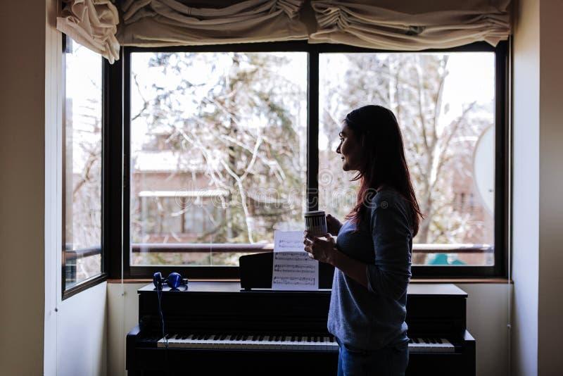 年轻女人拿着一杯咖啡的和准备好通过读音乐纸张弹钢琴 户内音乐概念 库存图片