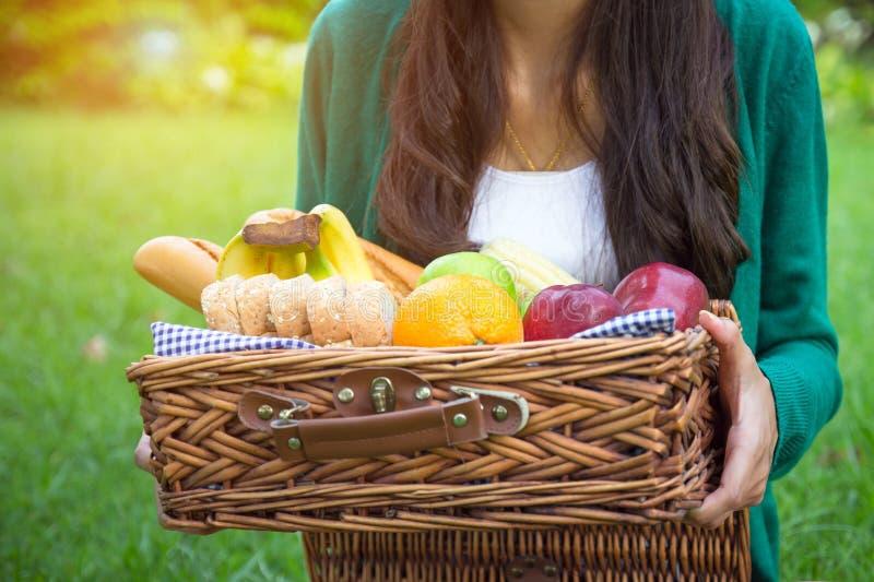 年轻女人拿着与健康食品、香蕉、苹果、桔子、玉米、全麦面包蔬菜和水果的秸杆篮子 库存图片