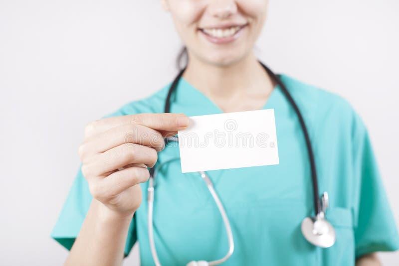 年轻女人拿着在灰色背景的医生手空插件 免版税库存照片